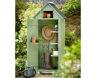 potting shed for against yellow fence beside side path near utility to right of cherry tree