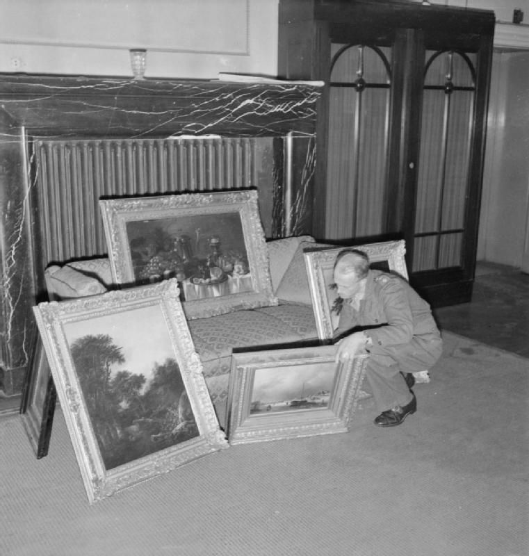 Captain H H Davies of Birkenhead, checks a collection of paintings found in the house of a member of the SS in Hanover who had looted them from The Netherlands. Captain Davies was in charge of the Property Control Department of the Military Government, his job being to take over Nazi controlled buildings and property, including looted works of art. The latter were held for safe keeping until returned in due course to their rightful owners.