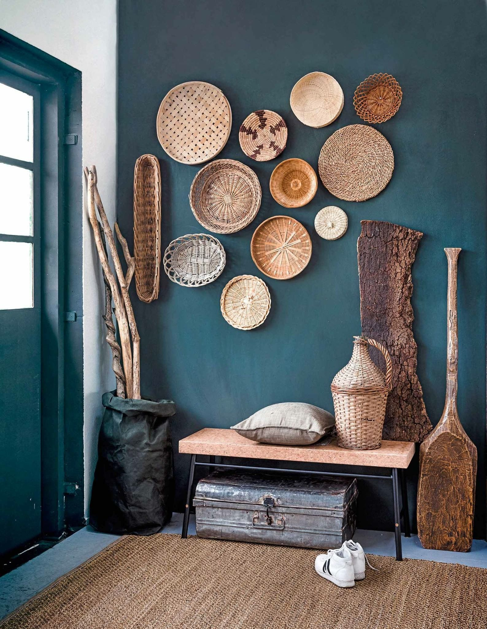 Baskets on teal wall entryway with lots of textures decoración