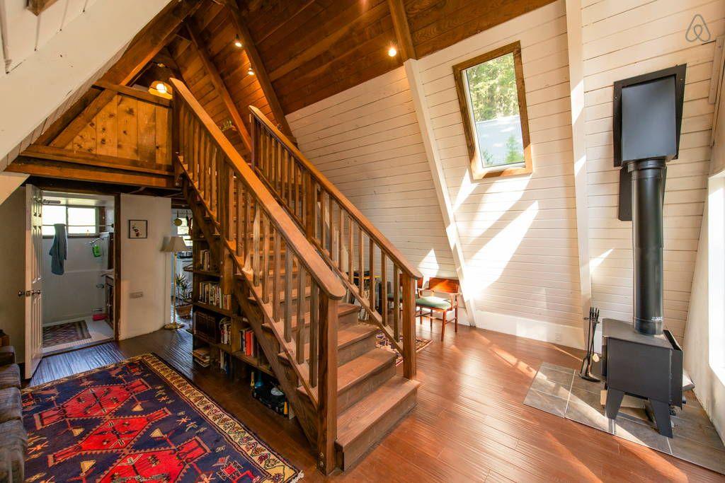 森の中に建つコンパクトなAフレームの山小屋 玄関から入ったところ 中央に階段、その下は本棚と収納棚.jpg