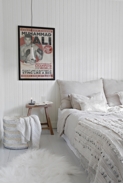 all white bedroom with white wood paneled walls. wall art is only ...