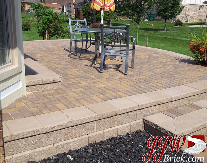 raised brick paver patio with unilock pisa ii retaining wall and classic 4x8 paver stones - Brick Paver Patio Designs