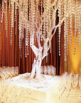 Brides.com: . Simple centerpieces succeed with a single eye-catching installation, such as this crystal-festooned tree, as the party's focal point. The main attraction: Manzanita branches—spray-painted silver, and dripping with crystal ropes—sit atop a special champagne bar (or escort card station). Tree by Geoff Howell. Crystals, from Swarovski crystal components. Site, Twenty Four Fifth Avenue, New York City.
