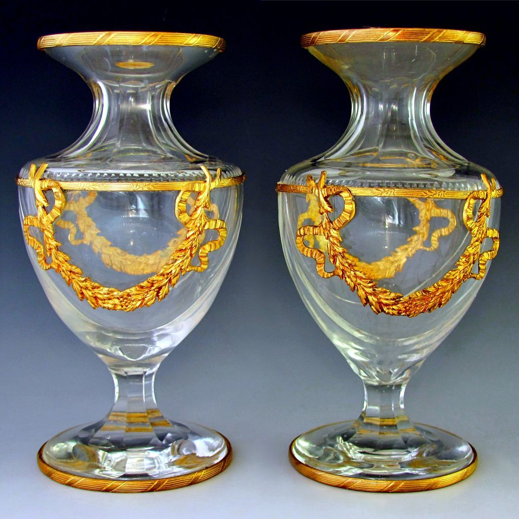 fine pair of antique 19th century French Empire gilt bronze and cut crystal vases. The bodies are of thick crystal in a classic baluster-form with deeply cut swag accenting, fluted neck and base, and zipper notching at the collar. Superb quality, an old unsigned Baccarat as the firm used paper labels from 1860 on, which often got worn or washed away, and did not use their acid etched signature until 1936. From The Antique Boutique, www.theantiqueboutique.rubylane.com