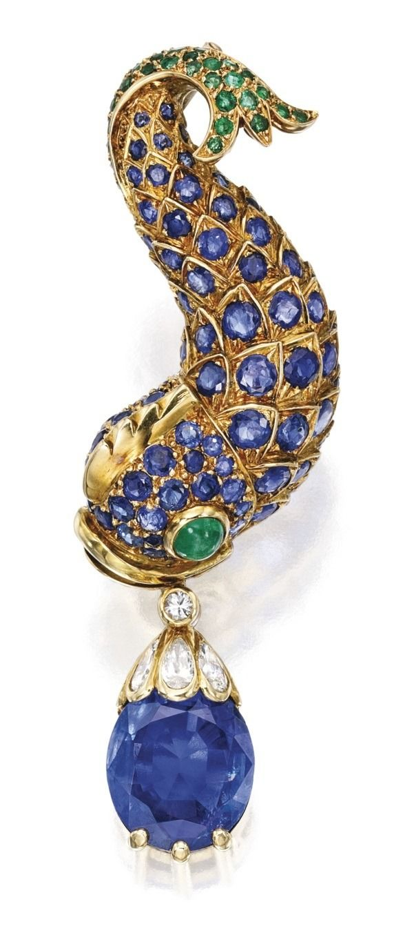 18 Karat Gold, Gem-Set and Diamond Brooch, René Boivin, France. Designed as a dolphin set with round sapphires and emeralds, with a cabochon emerald eye, suspending an oval-shaped sapphire weighing...