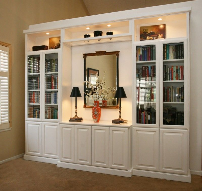 white wooden built in niches with shelves and cabinet in ...