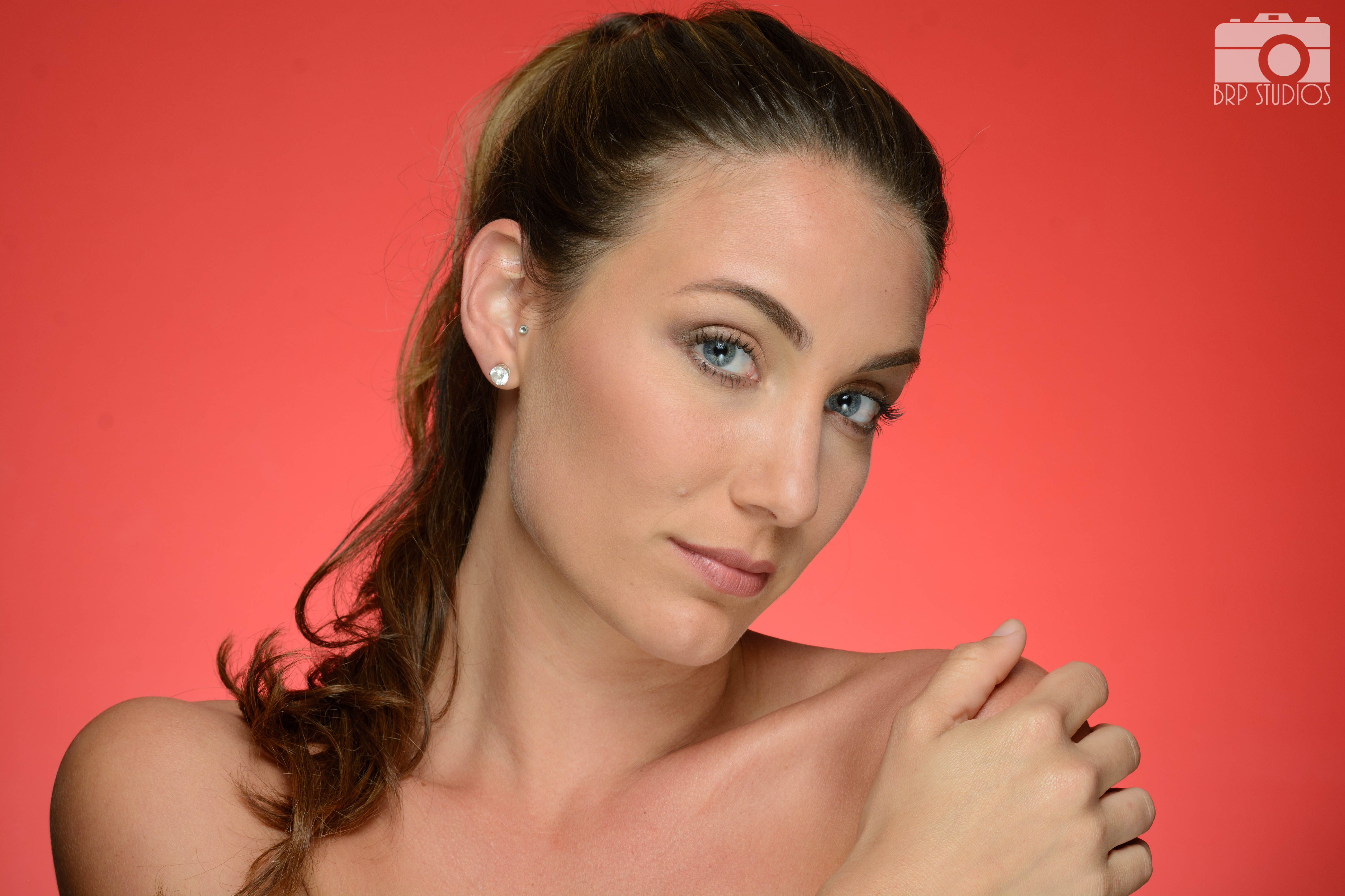 2 light setup - beauty dish directly over model with reflector below her and 1 light for backdrop feathered upwards