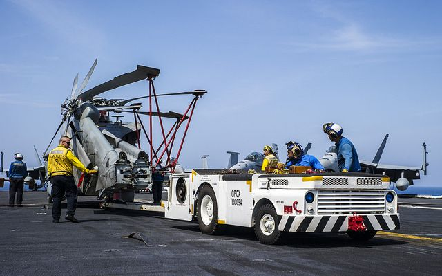 """PACIFIC OCEAN (May 29, 2014) Sailors transport an MH-60R Seahawk from the """"Saberhawks"""" of Helicopter Maritime Strike Squadron (HSM) 77 across the flight deck of the U.S. Navy's forward-deployed aircraft carrier USS George Washington (CVN 73). (U.S. Navy photo by Mass Communication Specialist 3rd Chris Cavagnaro/RELEASED)"""