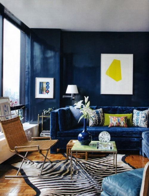 Glossy navy blue lacquer contrast so nicely against the ink blue velvet  sectional in this New York living room by Todd Alexander Romano.