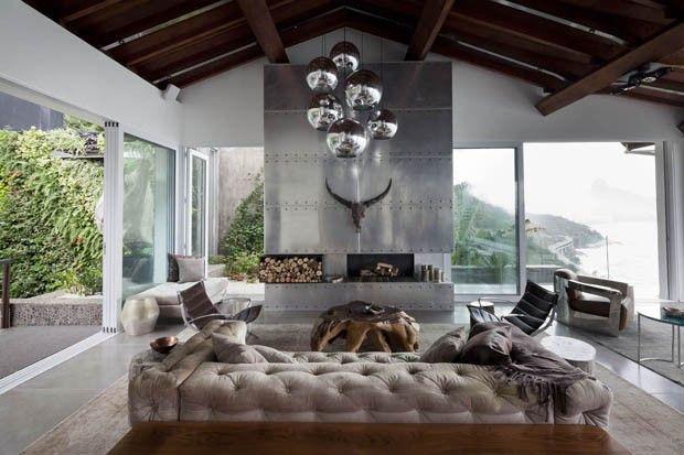 A sala de estar tem lareira revestida de painéis de aço, cabeça de touro balinesa, lustres de metal vindos de Hong Kong, sofá de veludo forrado pela Domme e poltronas da Ornare (Foto: Filippo Bamberghi)