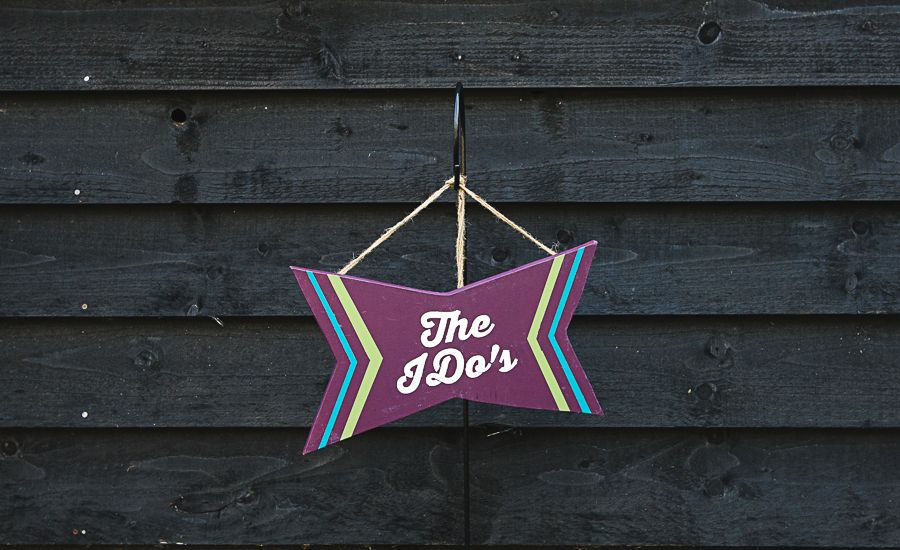 "Angular wooden sign painted in deep purple with blue and green accents, reading ""The I Dos"" in a modern font. A decorative sign for hanging, offering a lighthearted way to signal the ceremony space to guests. Perfect for both indoor and outdoor ceremonies. Designed and produced by Pocketful of Dreams, this is exclusively available from [&hellip"