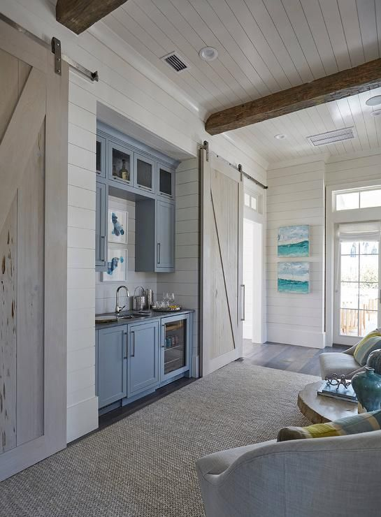 Beach style hallway boasts rustic wood beam ceiling as well as a nook filled with a blue wet bar filled with blue cabinets fitted with a square bar sink placed next to a glass front beverage fridge flanked by rooms finished with pecky cypress barn doors on rails.