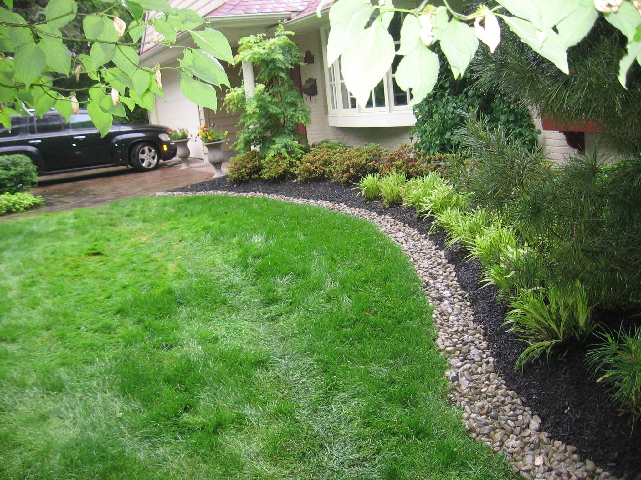 Front yard bed lined with river stone and mulch to create a clean space for  beautifully installed plants, grasses, and trees. Idea for our yard using  the ...
