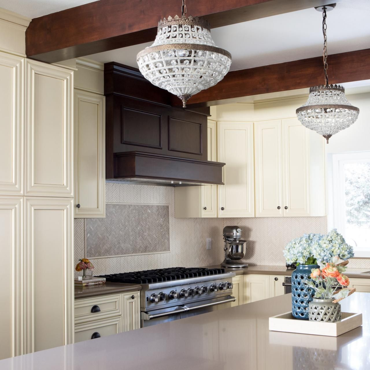 This traditional kitchen keeps things minimal and clean two this traditional kitchen keeps things minimal and clean two miniature chandeliers hang from the ceiling arubaitofo Choice Image