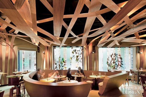 """Firm: El Equipo Creativo. Site: Barcelona, Spain. Idea: The 2,700-square-foot interior of Ikibana restaurant references Japanese flower-arranging, using all parts of a plant to emphasize line and form: petal-shape tables, decorative foliage and a canopy of sinuous hardwood """"branches."""""""
