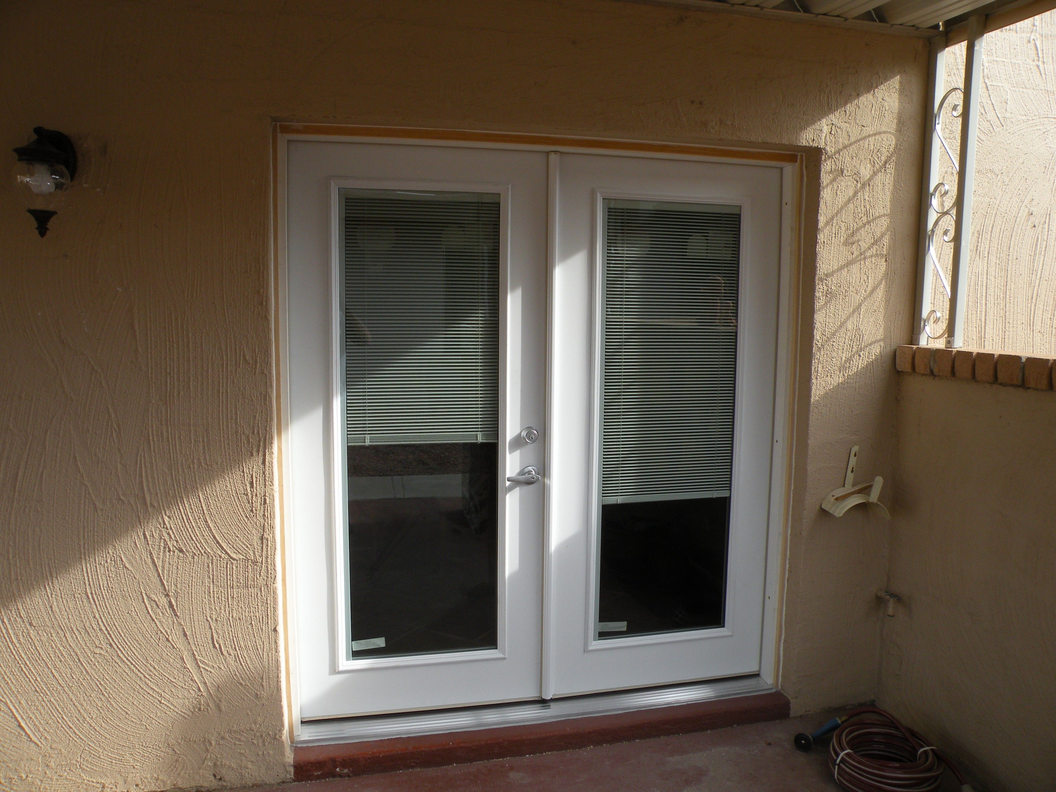 Interior white venetian blinds on bi fold white framed glass door