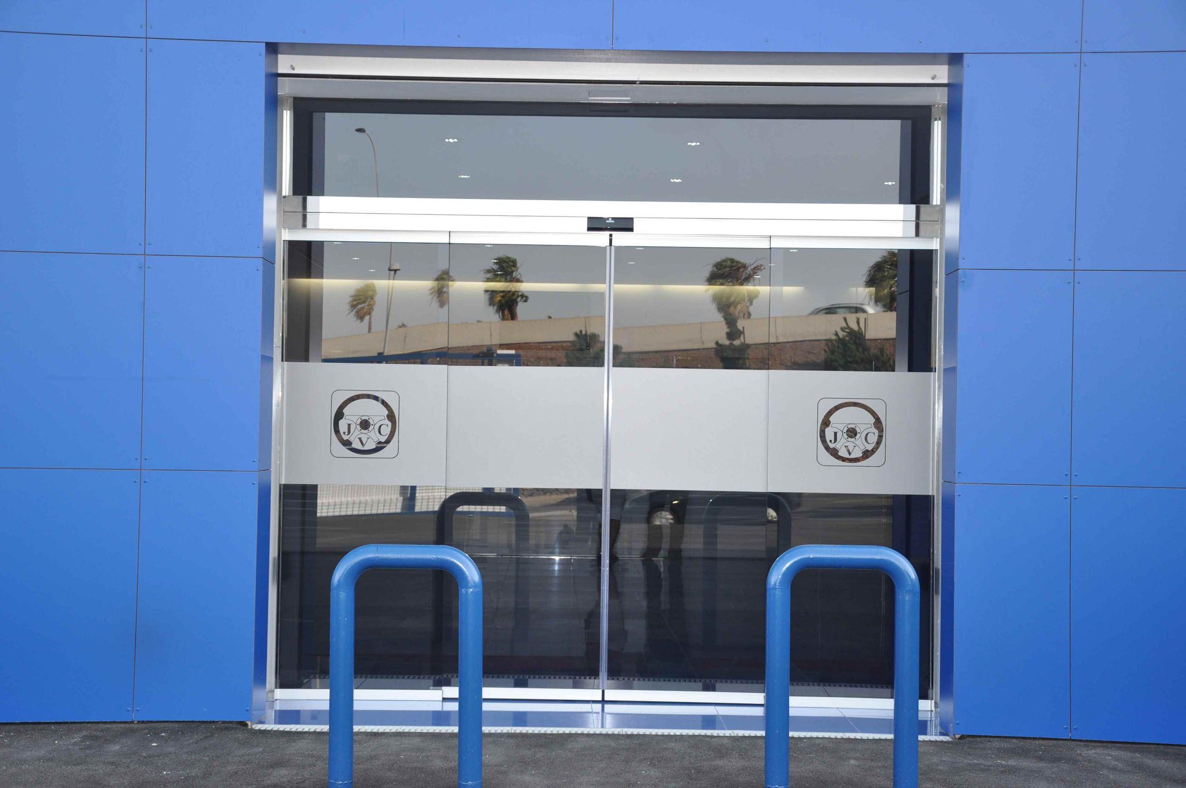 Puerta automática en cristal templado y acero inoxidable. Tenerife