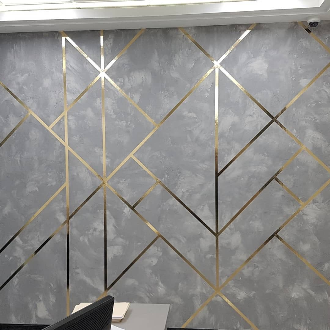 Concrete textured wall with golden geometrical lin