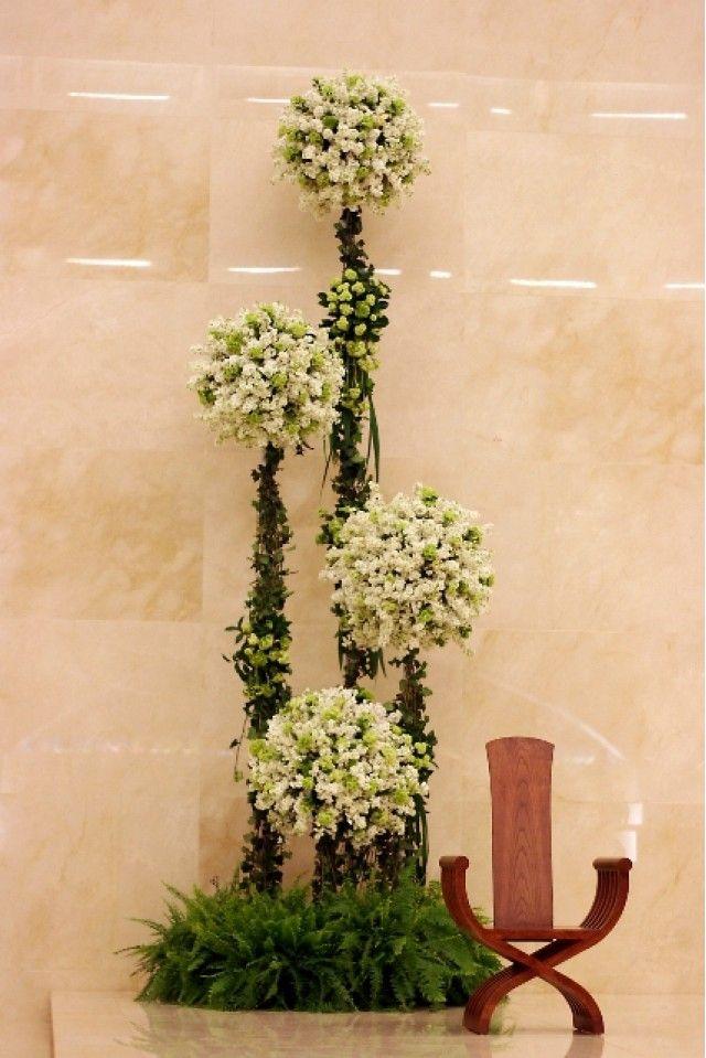 Altos y majestuosos topíaris que fueron colocados sobre unas bases - decorar jarrones altos