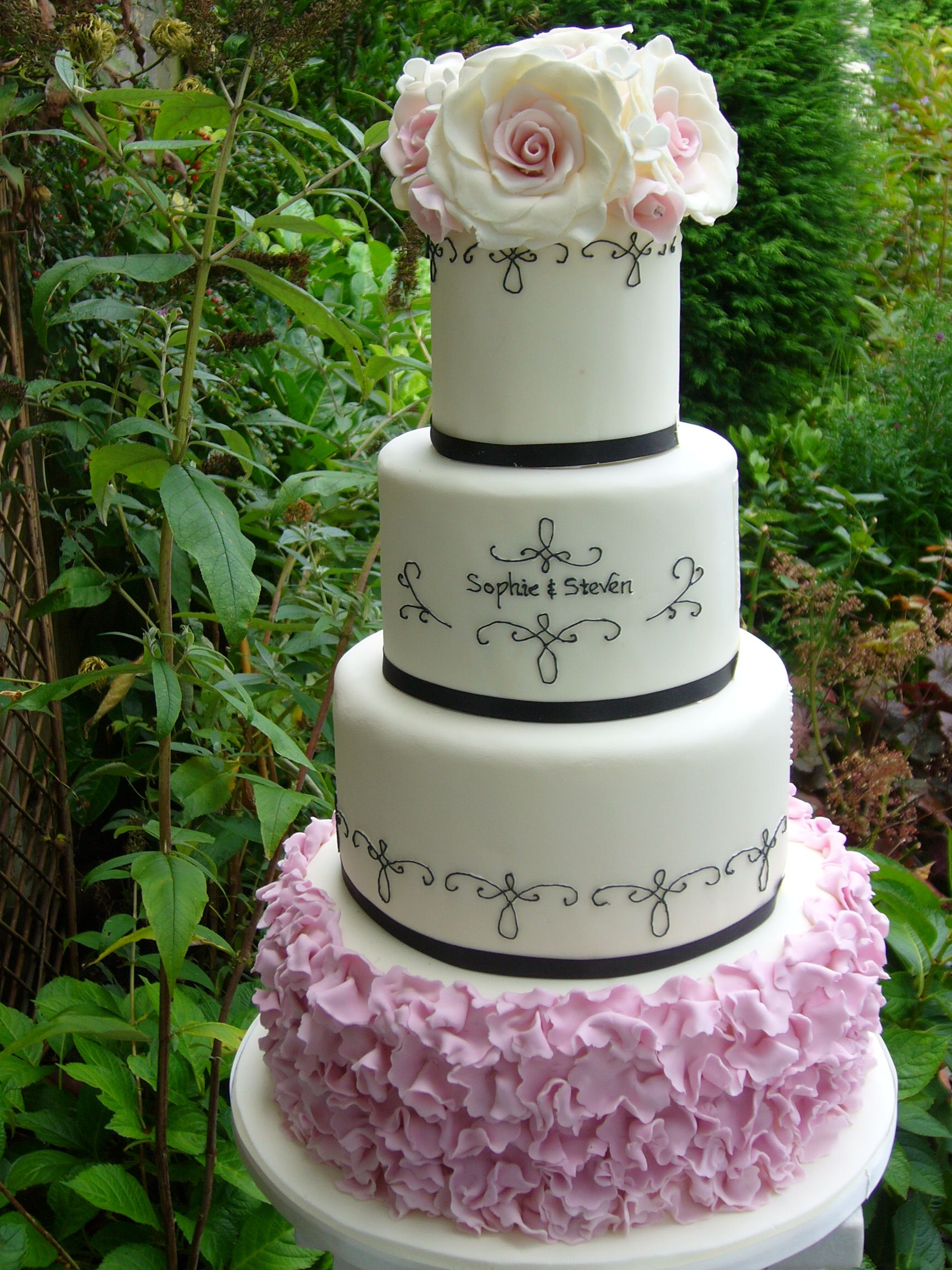 New design four tier wedding cake with ruffles black piping with