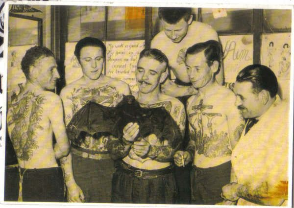 1950s pic of Les Skuse and members of the Bristol Tattoo Club shows them holding their club's calling card. For recognition purposes, every member is secretly inked somewhere on their body with the club insignia -- a black bat.