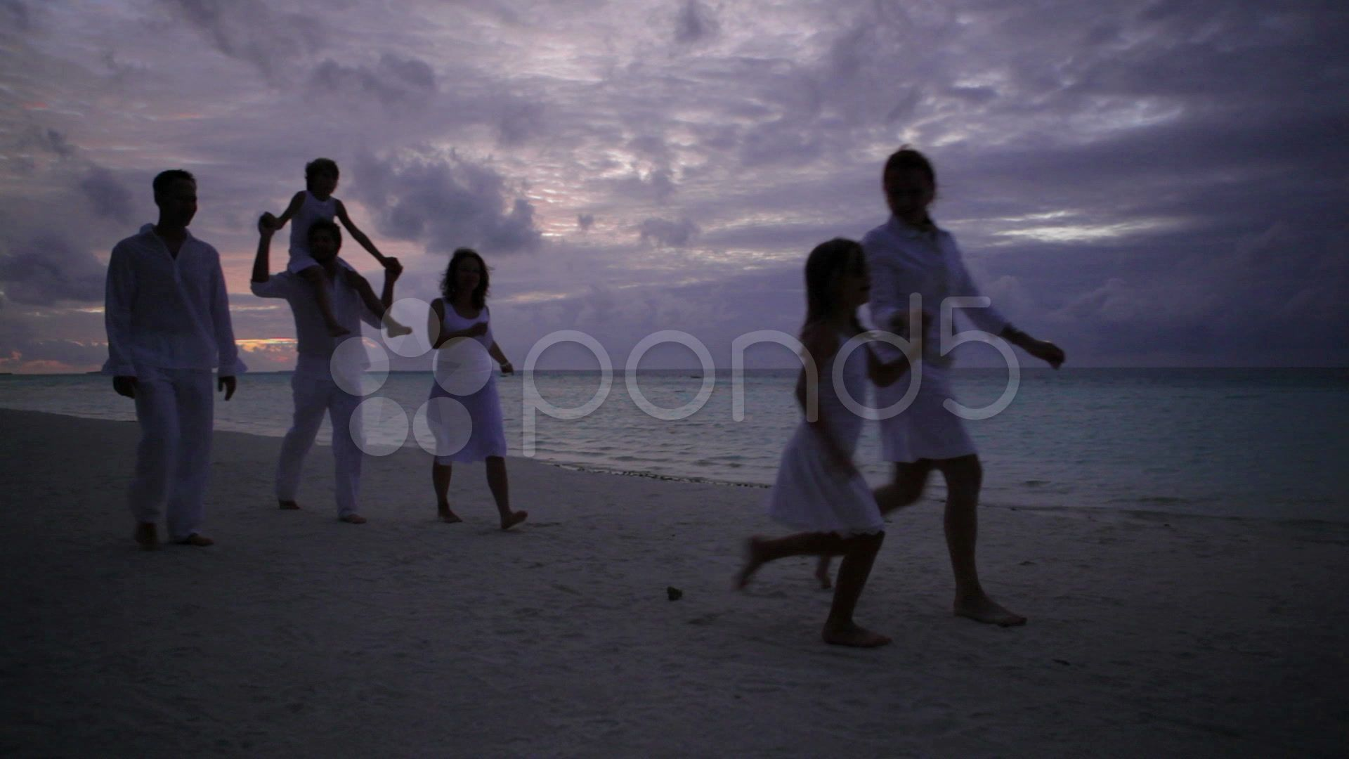 People walking on beach after sunset Stock Footage beachwalkingPeopleFootage