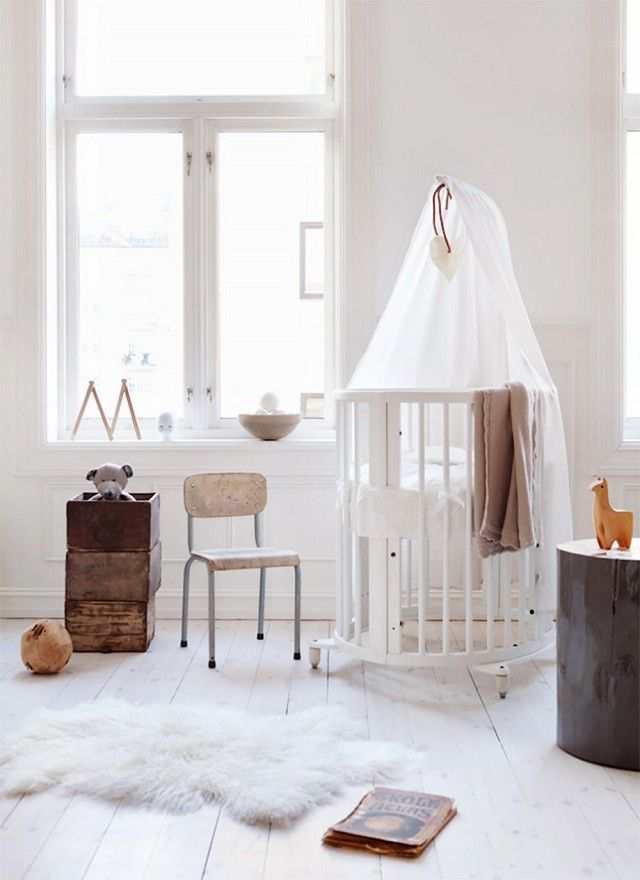 Minimalist inspired gender-neutral nursery with a white crib, touches of wood, and a lamb throw