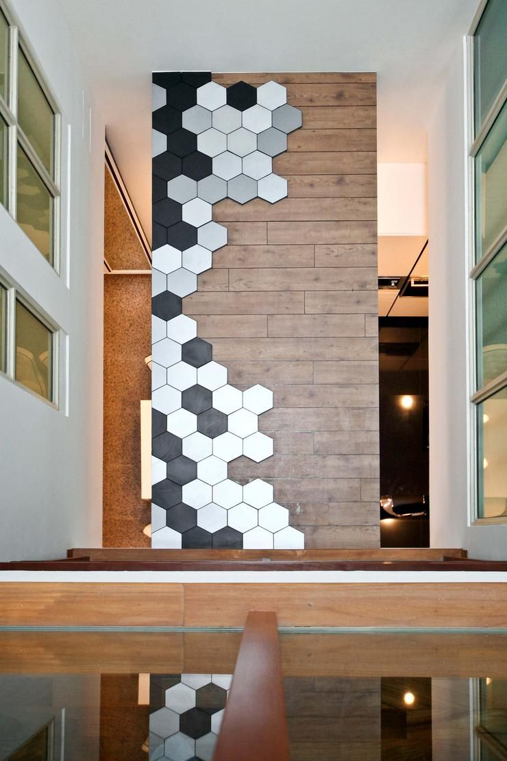 Mixed materials take cue from these owner who used a mix of wood and metal panels to create a feature wall the hexagonal panels also light up at night