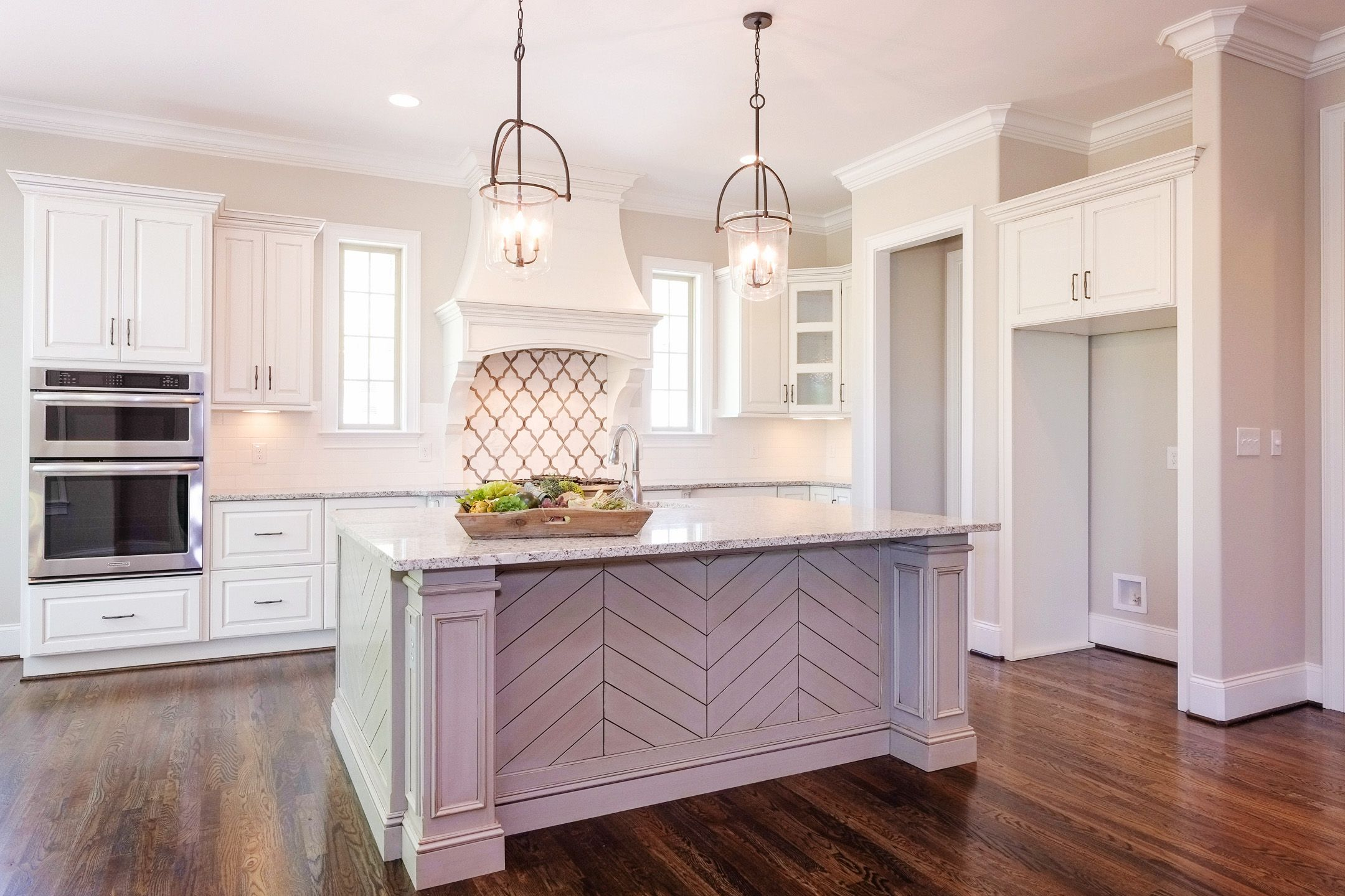 A Clean Slate White Cabinets And A Herringbone Accented Island And Bar This Airy Custom Kitchen Was Designed Custom Kitchen Custom Cabinetry Custom Cabinets
