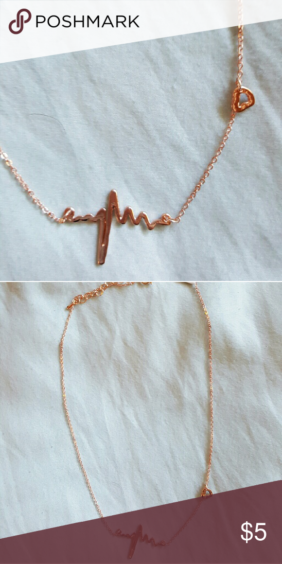 Heartbeat Necklace in Rose Gold/Copper Heartbeat Necklace in Rose Gold/Copper. Not real rose gold. Chain is fairly short. Would sit higher on collarbone. Heart Charm up one side of the chain. Jewelry Necklaces