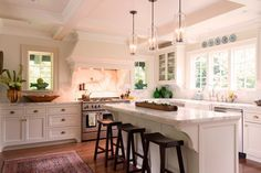 This kitchen was updated in a traditional, elegant style that pays homage to its 1900s roots. The light walls and white marble countertops brighten the space, and natural light from the large windows filters through the room. The island provides crucial work space as well as a place to sit and eat.