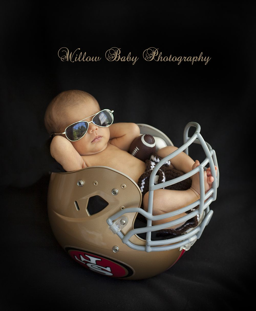 Newborn football picture with baby boy wearing sunglasses at Willow Baby Photography in San Jose
