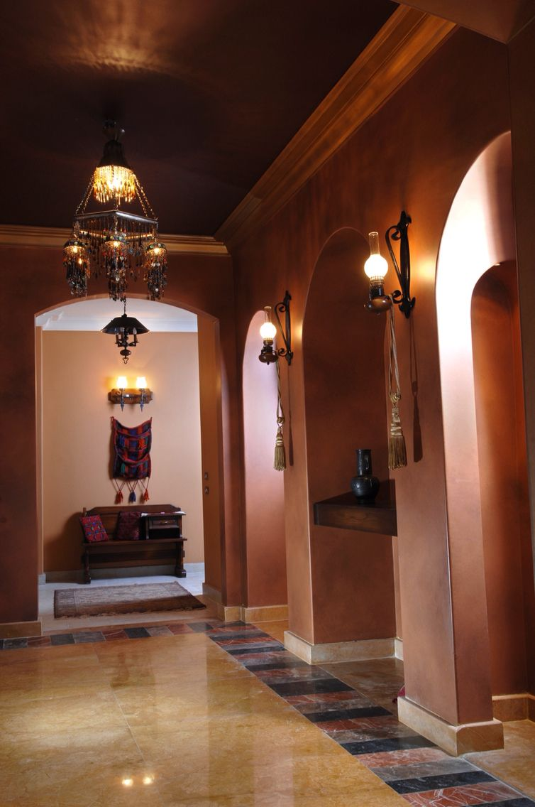 Ethnic entrance lobby with arched entryways and air sprayed walls and brass finish metal chandeliers
