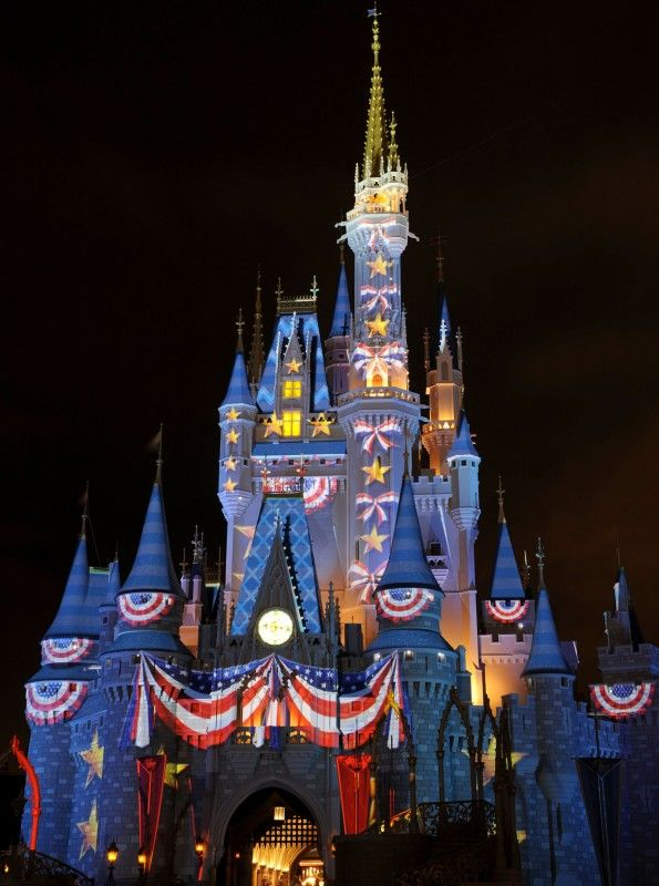 Red, White & (Bibbidi Bobbidi) Blue -- Illuminated image projections create the illusion of red, white and blue bunting on the exterior of Cinderella Castle at the Magic Kingdom theme park during July 4th celebration at Walt Disney World Resort in Lake Buena Vista, Fla.