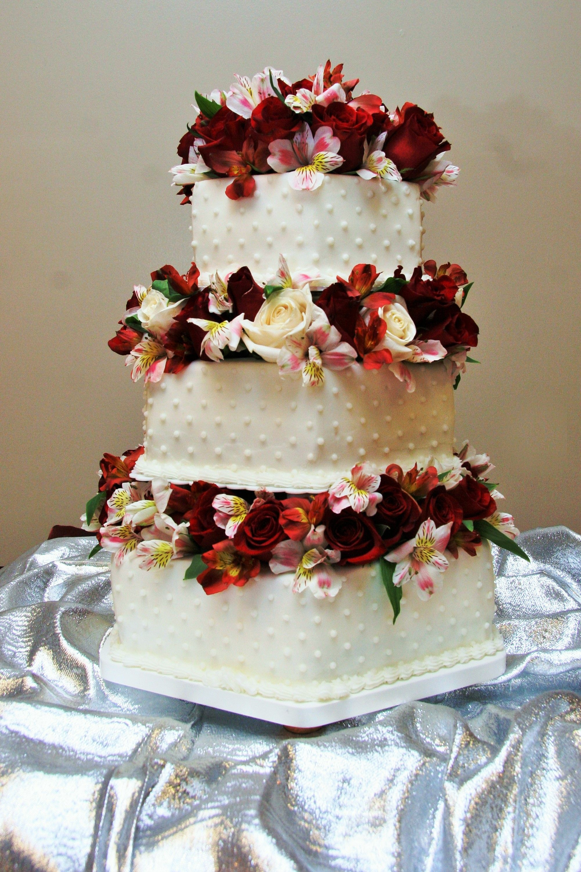 tier square wedding cake with small dot design and flowers