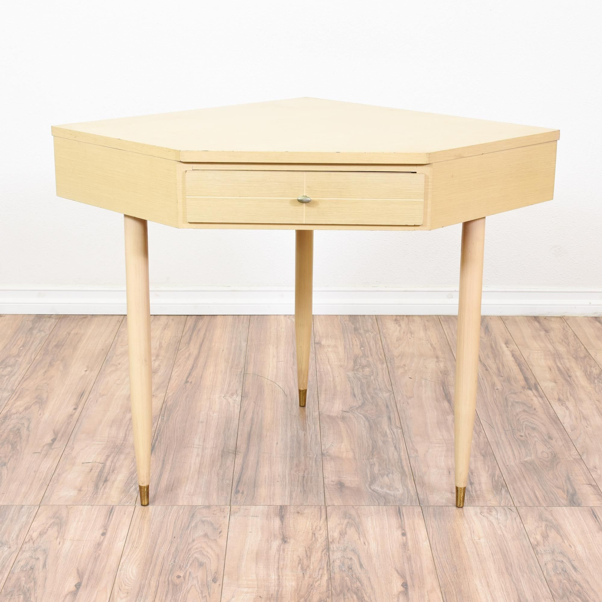 This mid century modern corner desk is featured in a solid wood with a light blonde
