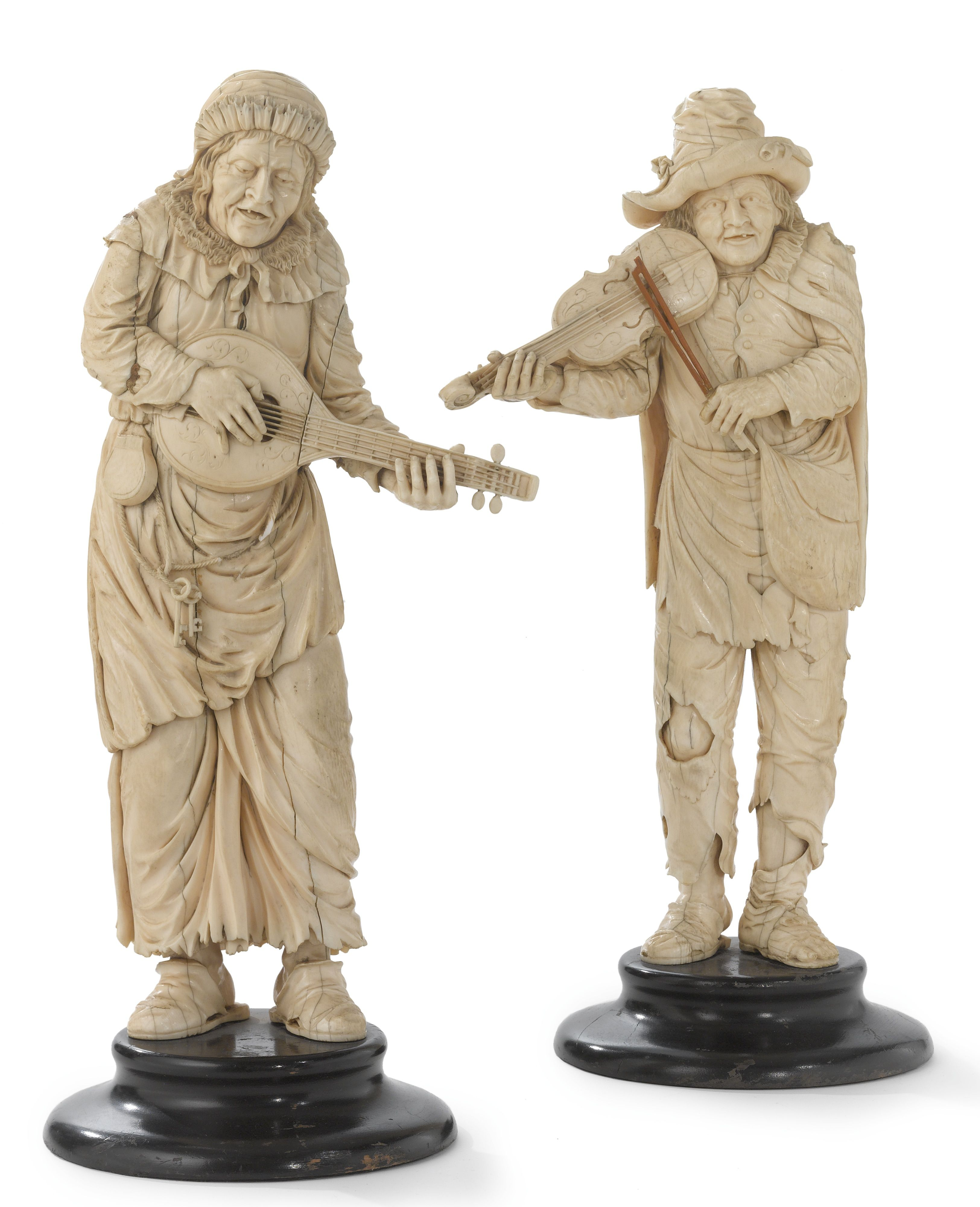 A PAIR OF CARVED IVORY FIGURES OF BEGGAR MUSICIANS IN THE MANNER OF SIMON TROGER, Germany, 2nd half 19th century.