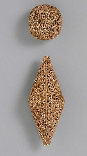 Two beads 11th century; Fatimid Syria, fabricated from wire and strips of sheet, decorated with granulation. These beads feature superb patterns of scrolling vines whose bifurcations elegantly extend the design to fit the required space. The patterns recall those of the beveled style of the ninth century, although these possess clearer lines, perhaps owing to the medium.
