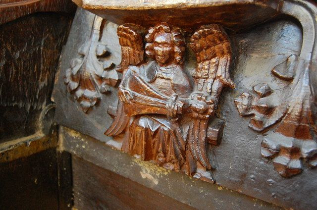 An angel plays a string instrument, Misericord, Great Malvern Priory (by Julian P Guffogg, geograph.co.uk 3087064 61ab78ac) - Category:Misericords in England - Wikimedia Commons