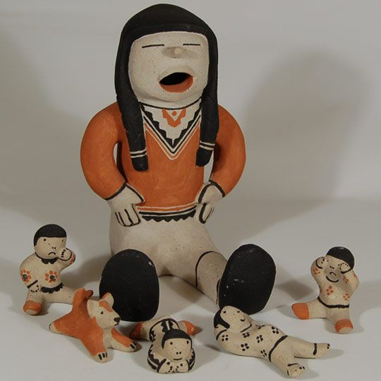 #adobegallery - Cochiti Pueblo Male Story Hour Figurine with 5 Listeners by Buffy Cordero Suina (1969-present) - Cochiti potter Buffy Cordero, granddaughter of the famed Helen Cordero, created this charming figure. It is a male figurine with a group of children and a dog sitting around listening to him tell stories.  This style figurine, with the children separate from the adult, has been named a Story Hour.