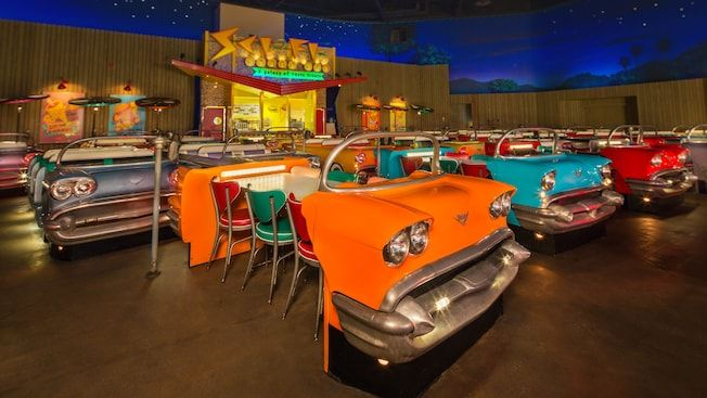 Close Up Of 1950s Car Dining Table With 3 Chairs And Snack Bar In Background