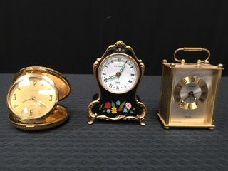 GROUPING OF THREE BEDSIDE CLOCKS INCLUDING A BUCHERER MUSICAL BLUE DANUBE CLOCK BY LADOR SWITZERLAND, A GERMAN DELUXE 7 JEWELS COMPACT SIZE TRAVEL CLOCK AND A BRASS LINDEN MINIATURE CLOCK. ALL PIECES MEASURE AROUND 3.5 INCHES HIGH.