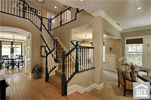 the contrast of black tan and white. Huge open concept main floor with open staircase through the middle.