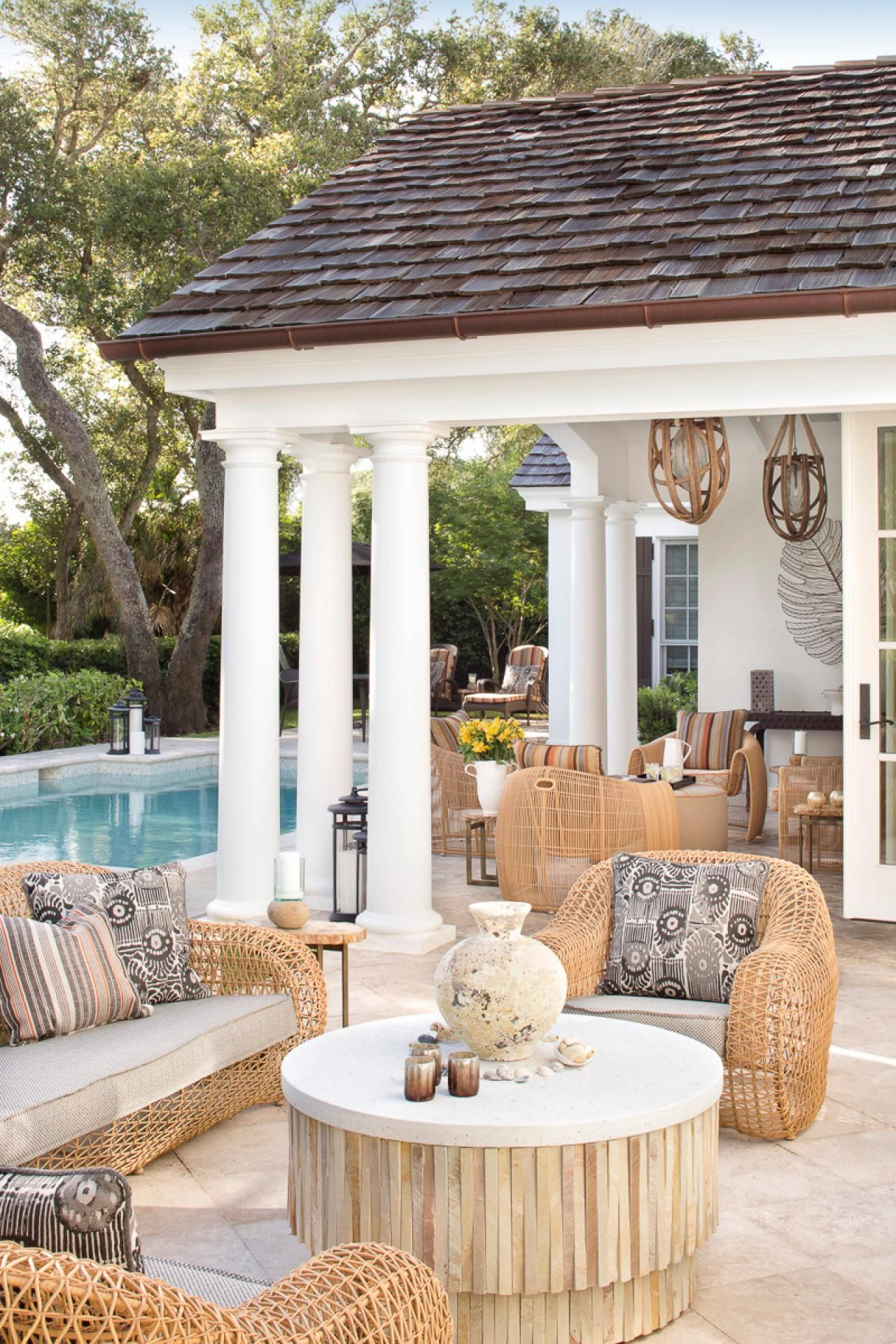 Enjoy the scenery and the pool in this tropical backyard. Wicker chairs, bold decorative patterns and a thatched coffee table are all included in this outdoor seating area.