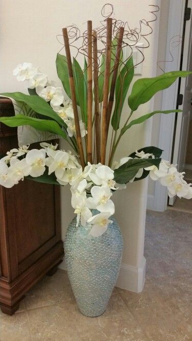 Diy floral arrangement with orchids in a turquoise glass