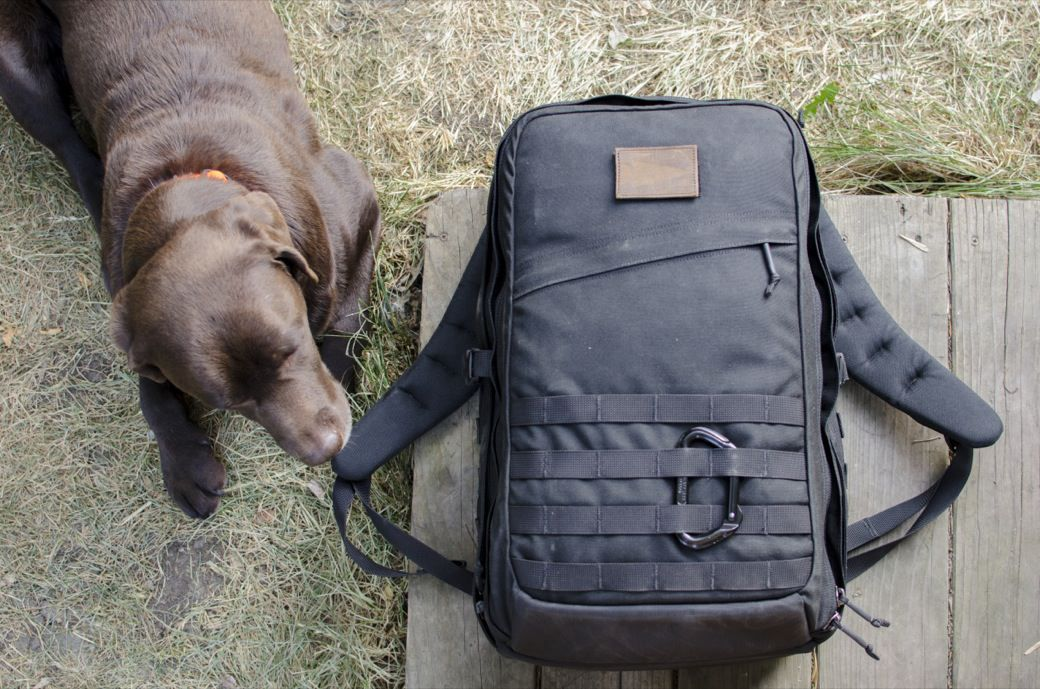 GORUCK GR2 Travel Backpack laying on the ground next to a dog. It ...