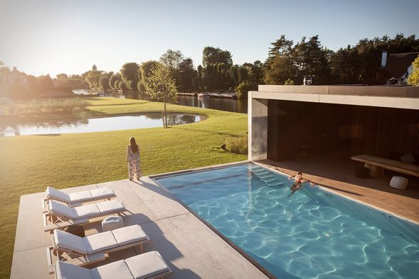 This impressive villa is the ultimate bachelor pad. Located near the Belgian city of Gent, this mind-blowing property lays on the quiet banks of the river Leie, a place well known for its leisure boating. The sculptural concrete bachelor pad was desi