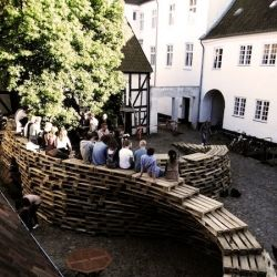"""Designed and built by Aarhus School of Architecture students in Danemark, """"Be Paletto"""" is a temporary pavilion made of hundreds of overlapped wooden pallets. Between architecture and furniture."""