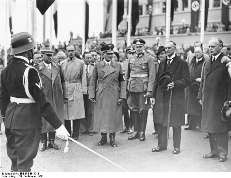 """Officer commanding honor of the SS Standarte """"Germany"""" salutes visiting English Prime Minister Chamberlain (center with umbrella). Others in the photo Reich Foreign Minister von Ribbentrop (right)  Reich Governor Ritter von Epp and the Bavarian Prime Minister Siebert (in long overcoat), 30 Sept 1938."""