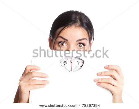beautiful young scared  woman  holding scales, isolated against white background - stock photo